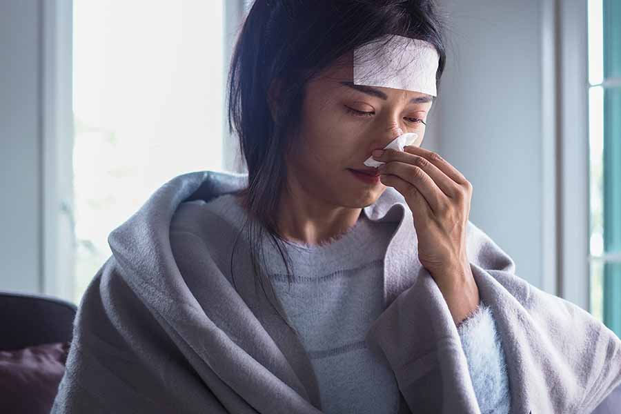 lady suffering from cold, runny nose and fever