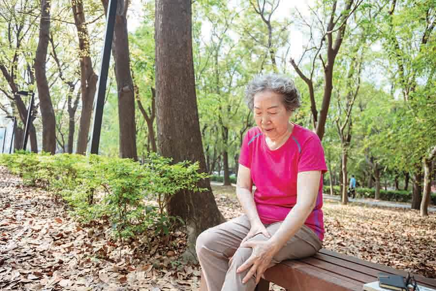 Elderly woman sitting on a bench due to joint pain